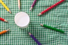 Молоко на зеленых скатертях и crayons Стоковые Изображения