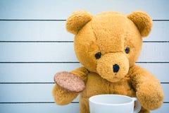 Молоко питья плюшевого медвежонка с печеньями на деревянной предпосылке Стоковые Изображения