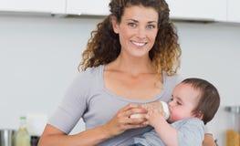 Молоко привлекательной женщины подавая к младенцу Стоковые Изображения RF
