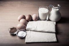 Молоко, сахар, какао, тесто слойки, яичка и соль на деревянной доске Стоковые Изображения