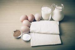 Молоко, сахар, какао, тесто слойки, яичка и соль на деревянной доске Стоковое фото RF