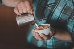 Молоко Barista лить в кофе в чашке стоковая фотография
