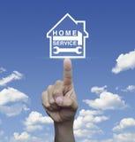 Молоток и ключ отжимать руки с значком дома над wi голубого неба Стоковые Изображения