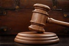 Молоток судьи на коричневой деревянной предпосылке стоковое фото