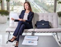 Молодая азиатская бизнес-леди в костюме смотря диаграмму на листе Стоковые Изображения RF