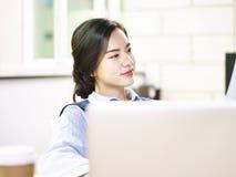 Молодая азиатская бизнес-леди сидя в офисе Стоковые Фотографии RF