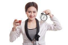 Молодая азиатская бизнес-леди с соком и часами томата Стоковые Фото