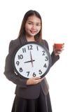 Молодая азиатская бизнес-леди с соком и часами томата Стоковые Изображения