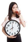 Молодая азиатская бизнес-леди с соком и часами томата Стоковая Фотография