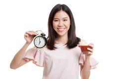 Молодая азиатская бизнес-леди с соком и часами томата Стоковые Изображения RF