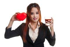 Молодая азиатская бизнес-леди с соком томата и красным сердцем Стоковая Фотография RF