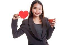 Молодая азиатская бизнес-леди с соком томата и красным сердцем Стоковое фото RF