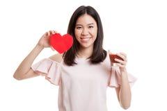 Молодая азиатская бизнес-леди с соком томата и красным сердцем Стоковое Изображение