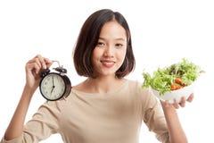 Молодая азиатская бизнес-леди с часами и салатом стоковая фотография rf