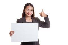 Молодая азиатская выставка бизнес-леди thumbs вверх с белым пустым знаком Стоковые Фотографии RF