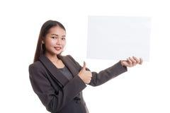 Молодая азиатская выставка бизнес-леди thumbs вверх с белым пустым знаком Стоковая Фотография