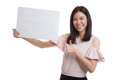 Молодая азиатская выставка бизнес-леди thumbs вверх с белым пустым знаком Стоковые Изображения RF
