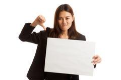 Молодая азиатская выставка бизнес-леди thumbs вниз с белым пробелом si Стоковая Фотография