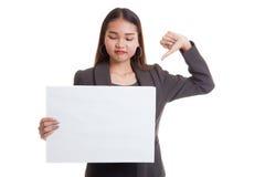 Молодая азиатская выставка бизнес-леди thumbs вниз с белым пробелом si Стоковые Фото