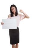 Молодая азиатская выставка бизнес-леди thumbs вниз с белым пробелом si Стоковые Фотографии RF