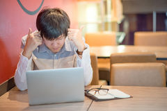 Молодая азиатская головная боль чувства человека во время работы Стоковые Фото