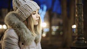 Молодая азиатская девушка смотрит в парке город на ноче на предпосылке освещает усмехаться на обеих сторонах видеоматериал