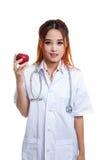 Молодая азиатская женская выставка улыбки доктора яблоко Стоковая Фотография