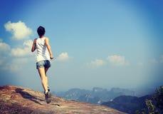 Молодая азиатская женщина бежать на горном пике стоковые фотографии rf