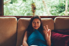 Молодая азиатская женщина во время каникул ослабляя на софе с большим окном за ей женщина на летних каникулах в Бали Стоковое Фото