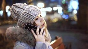 Молодая азиатская женщина говоря на умном телефоне, сидя на деревянной скамье в парке города на ноче видеоматериал