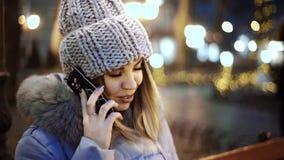 Молодая азиатская женщина говоря на умном телефоне, сидя на деревянной скамье в парке города на ноче сток-видео