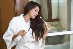 Молодая азиатская женщина держа зубную щетку и зубную пасту стоковые изображения