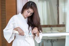 Молодая азиатская женщина держа зубную щетку и зубную пасту стоковые фотографии rf
