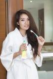 Молодая азиатская женщина держа зубную щетку и зубную пасту стоковое изображение rf