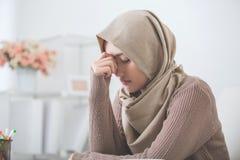 Молодая азиатская женщина держит ее голову думая о что-то стоковая фотография rf