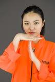 Молодая азиатская женщина делая время вне сигнализирует с руками в пленниках равномерных Стоковая Фотография RF