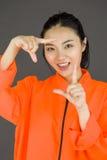 Молодая азиатская женщина делая рамку с пальцами в пленниках равномерный Стоковые Изображения
