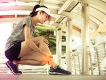 Молодая азиатская женщина имеет боль ног, после тренировки тренировки Lifest Стоковые Изображения RF