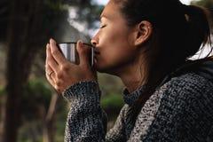 Молодая азиатская женщина имея кофе outdoors Стоковое Изображение