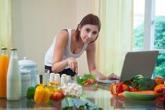 Молодая азиатская женщина ища рецепт Стоковые Фотографии RF