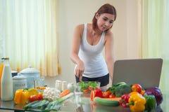 Молодая азиатская женщина ища рецепт Стоковые Фото
