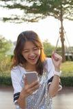 Молодая азиатская женщина наблюдая к экрану мобильного телефона с surprisi Стоковое фото RF