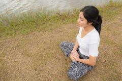 Молодая азиатская женщина наслаждаясь и ослабляя на зеленой траве стоковое изображение rf