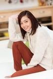 Молодая азиатская женщина ослабляя в живущей комнате Стоковые Фото