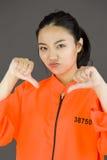 Молодая азиатская женщина показывая большие пальцы руки вниз подписывает от обеих рук в пленниках равномерных Стоковые Изображения RF