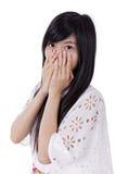 Молодая азиатская женщина покрывая ее рот Стоковое Изображение