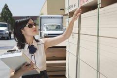 Молодая азиатская женщина проверяя деревянные планки на дворе тимберса Стоковая Фотография