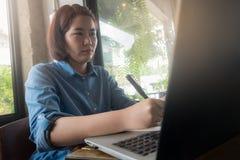 Молодая азиатская женщина работая в кофейне Стоковые Фото