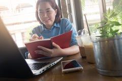 Молодая азиатская женщина работая в кофейне Стоковые Фотографии RF
