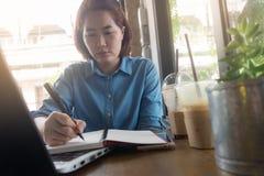 Молодая азиатская женщина работая в кофейне Стоковое Изображение RF